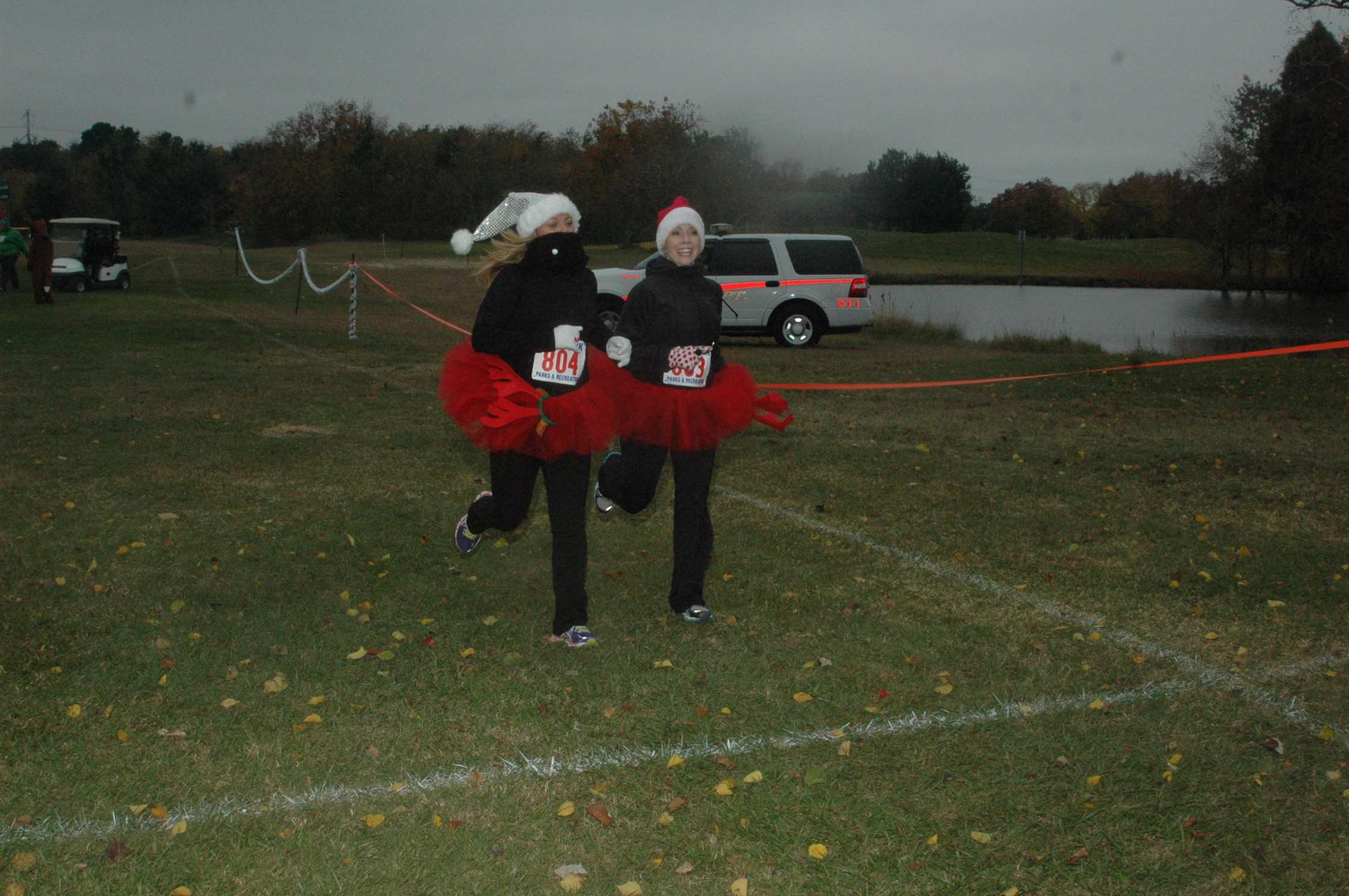 Two people running outside in Santa hats and Christmas red tutus