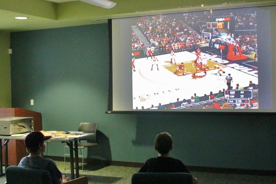 Teen Teens watching sport game on projector screen at Library