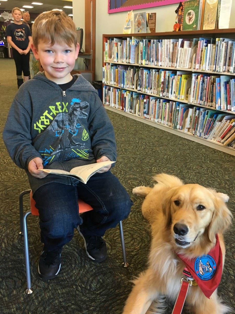 young boy sitting with book next to dog laying down
