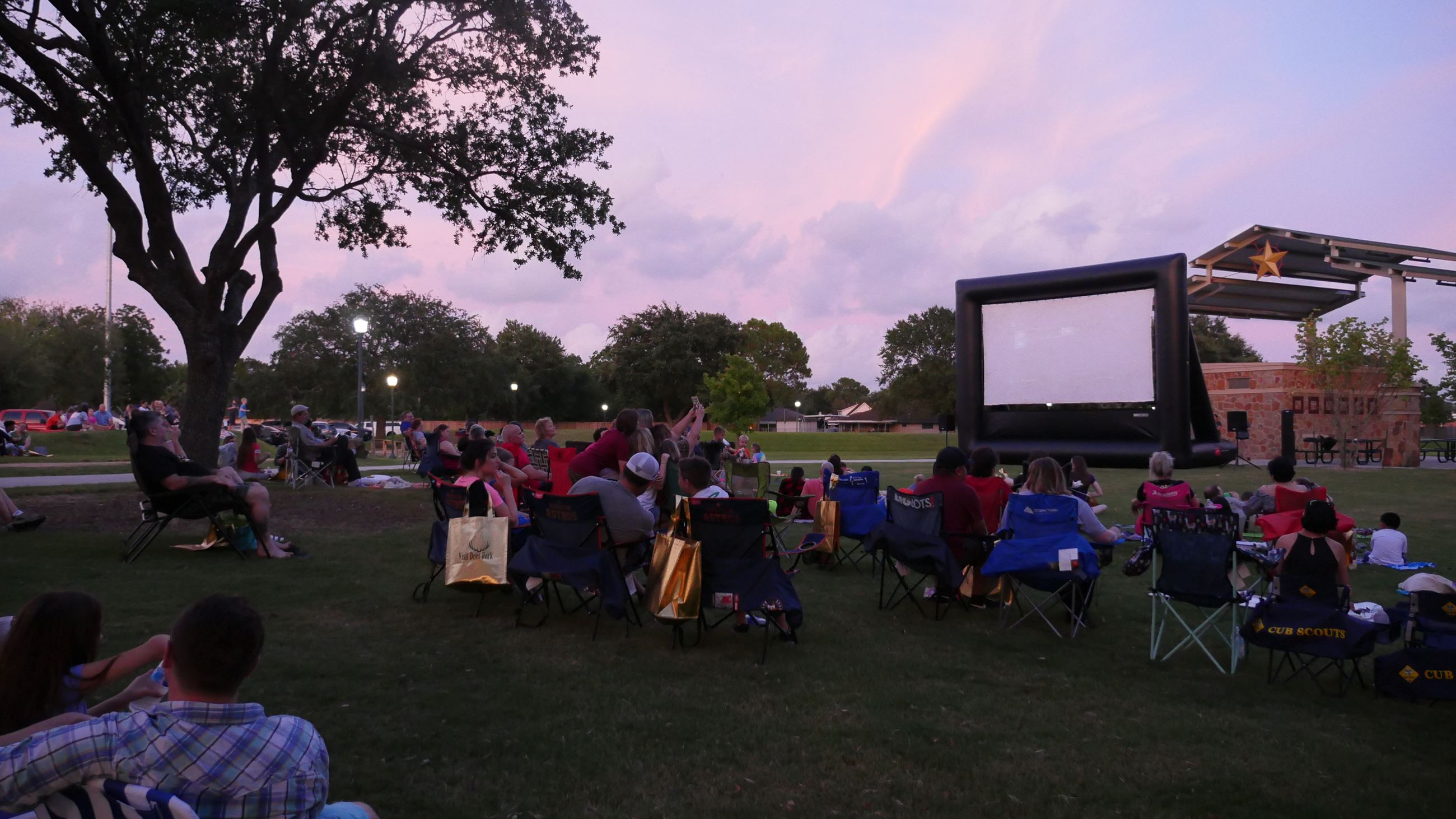 Movie screen with sunset behind it - families sitting on blankets outside watching movie